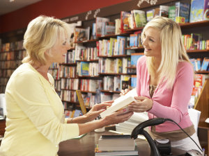 woman showing another woman a book in a book shop