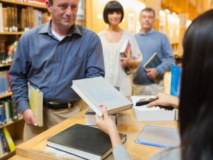 man purchasing book from bookstore with a queue