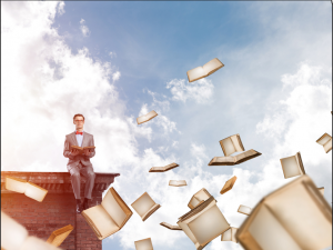 man sat on ledge reading a book with books flying around him