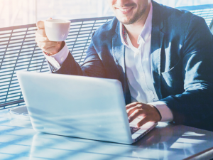 smiling man drinking coffee reading from a laptop