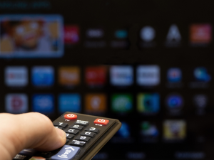 person using remote control to watch entertainment media