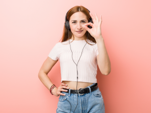 woman wearing headphones doing the ok sign